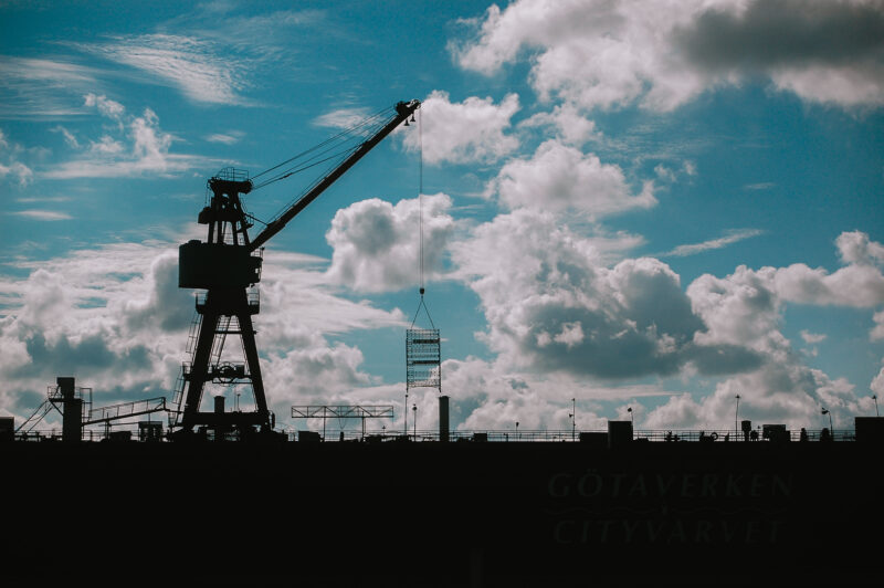 Large cranes against a blue sky with white clouds