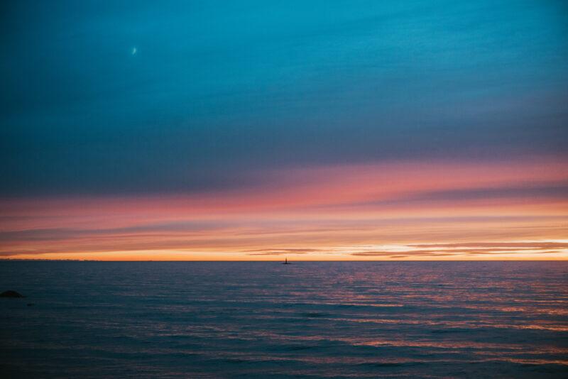A multi coloured sunset over a dark sea