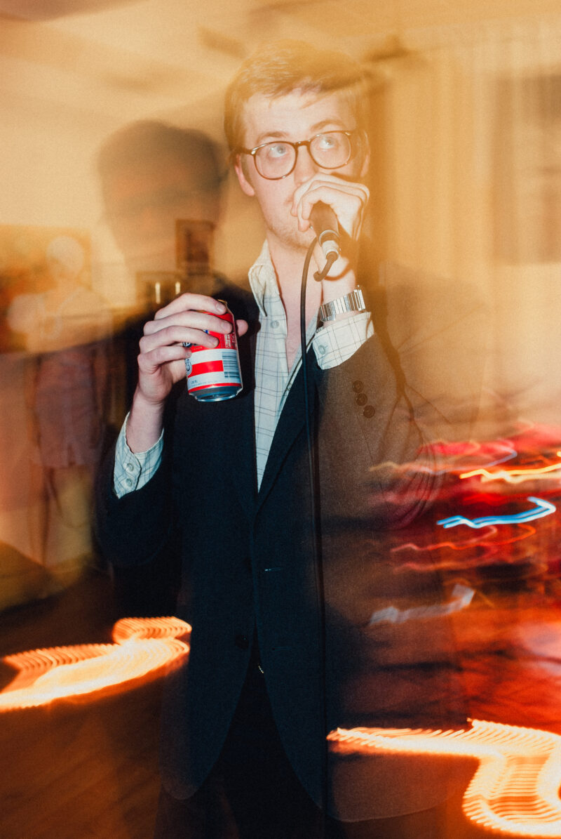 Musician James Ausfarth singing while holding a beer can