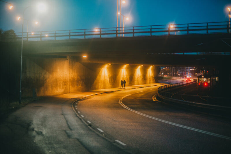 Two people walking under a viaduct