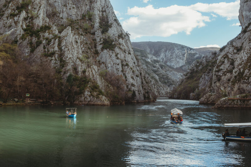 Small boats on Lake Matka surrounded by high mountains