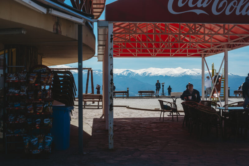 People sitting at a café, a snowy mountain is seen in the background