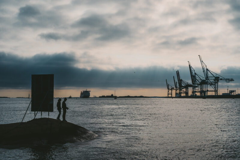 A couple fishing from a cliff in the sea. Some industrial cranes in the background.