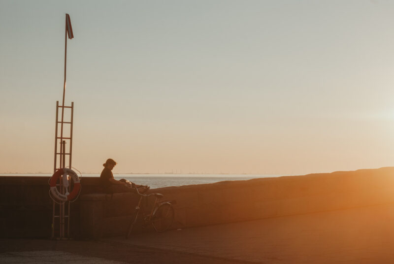Woman sitting on a wall during sunset