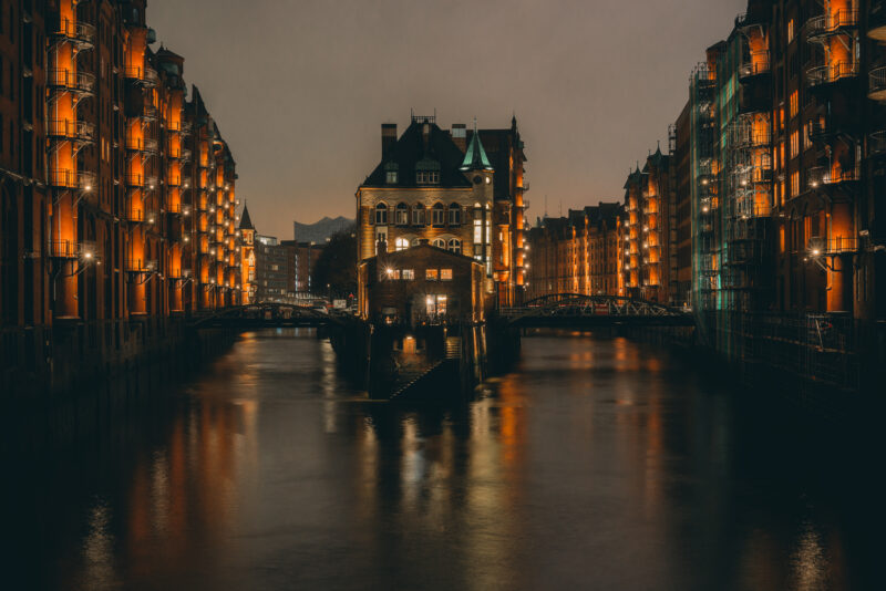 Houses in Speicherstadt (Hamburg) reflecting in the dark water of the channel.