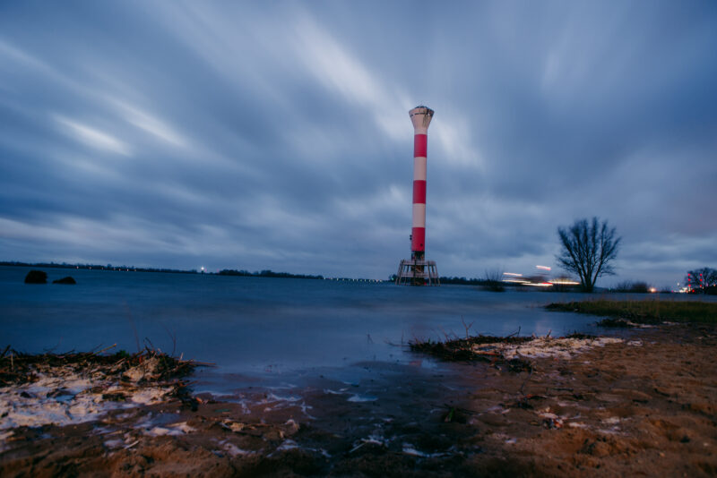 Red and white lighthouse on a flooded beach