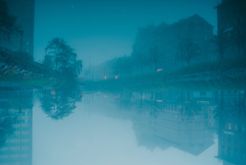 Houses reflecting in Malmö kanal during foggy weather