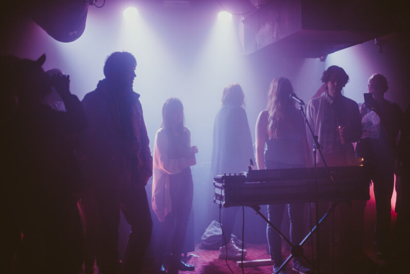 People standing on a stage filled with smoke