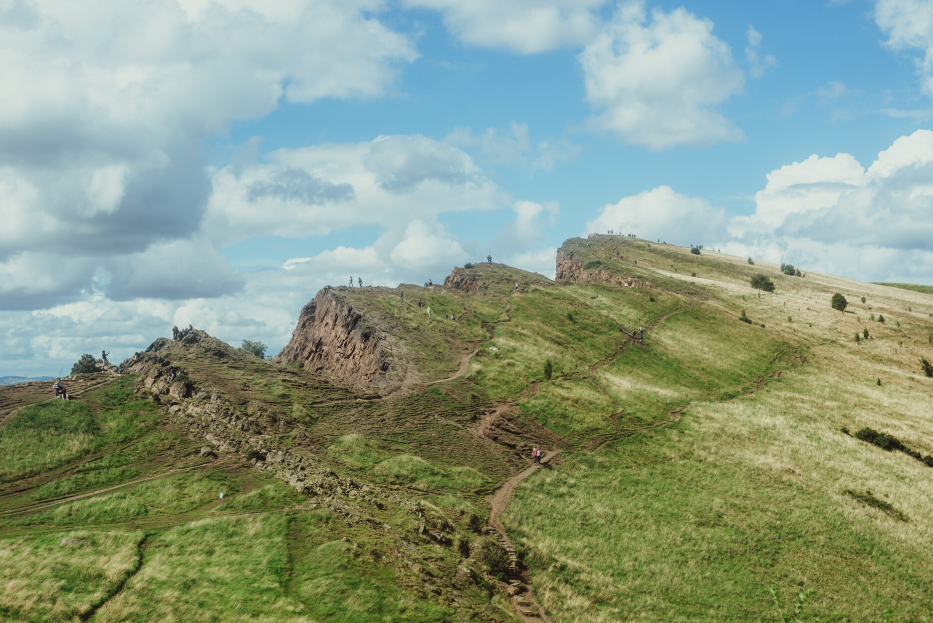 People walking the green heights of Arthur's seat