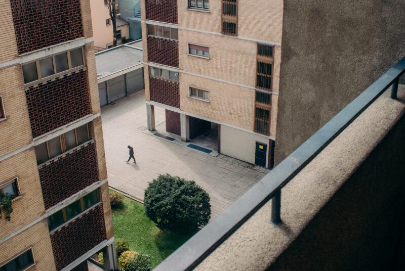 Bird's eye view of a young man walking between high rise buildings