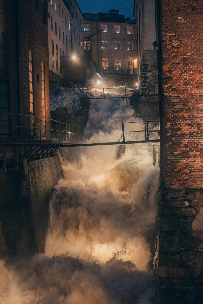 A steep water fall between old industrial buildings