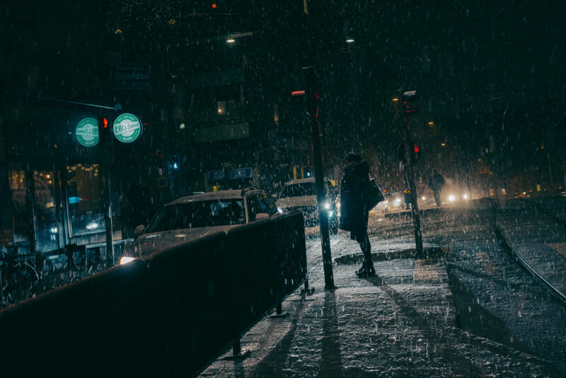 Snow falling over person standing at a pedestrian crossing