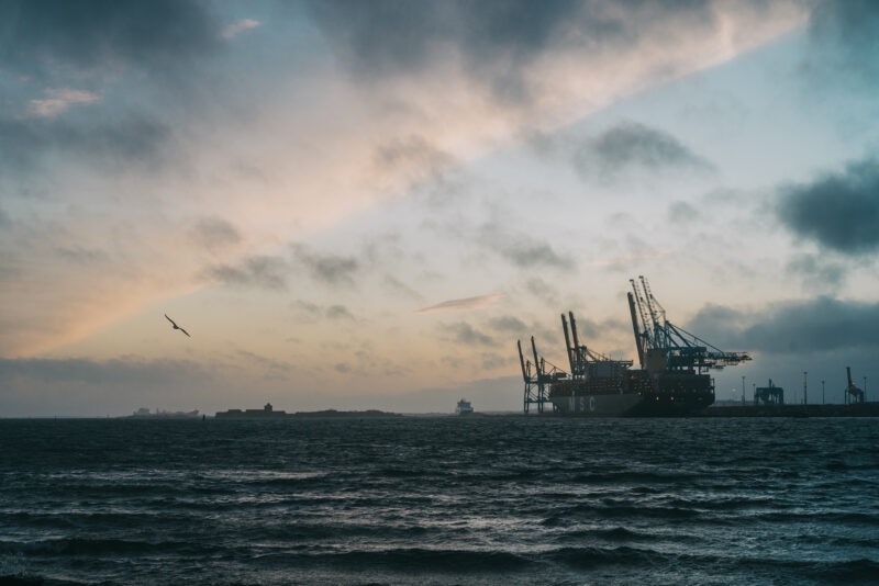 Dark water and large industrial cranes against a cloudy sky.