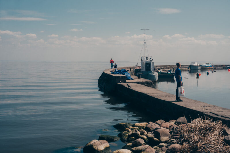 A stone pier and a few boats. A couple of people looking out over the Baltic Sea.