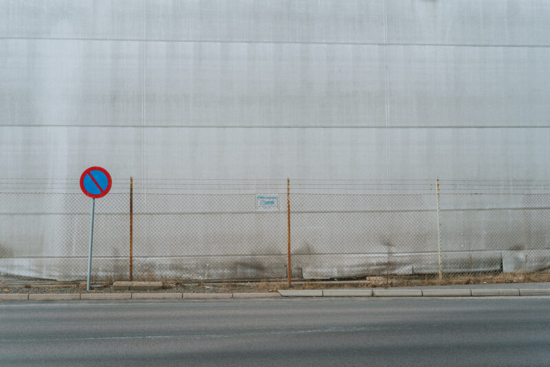 Traffic sign and fence against a grey wall