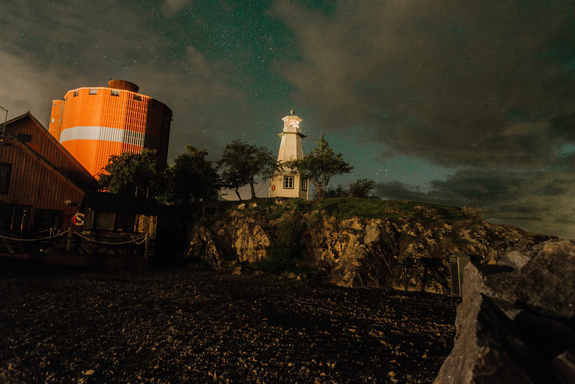 A silo and a lighthouse beneath a starry sky