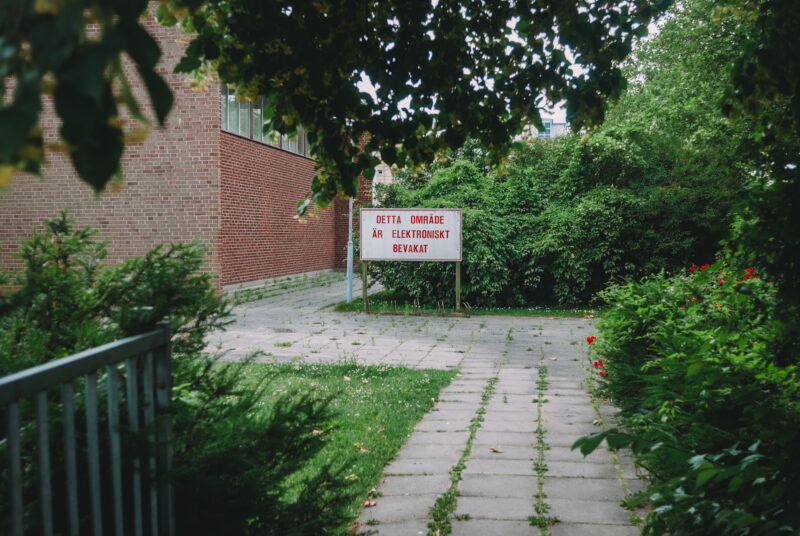 """A brick house, some bushes and a sign with the text """"Detta område är elektroniskt bevakat""""."""
