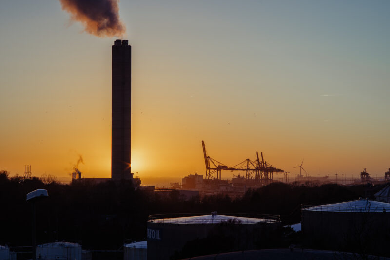Industrial buildings, cranes and a large chimney against a beautiful sunset