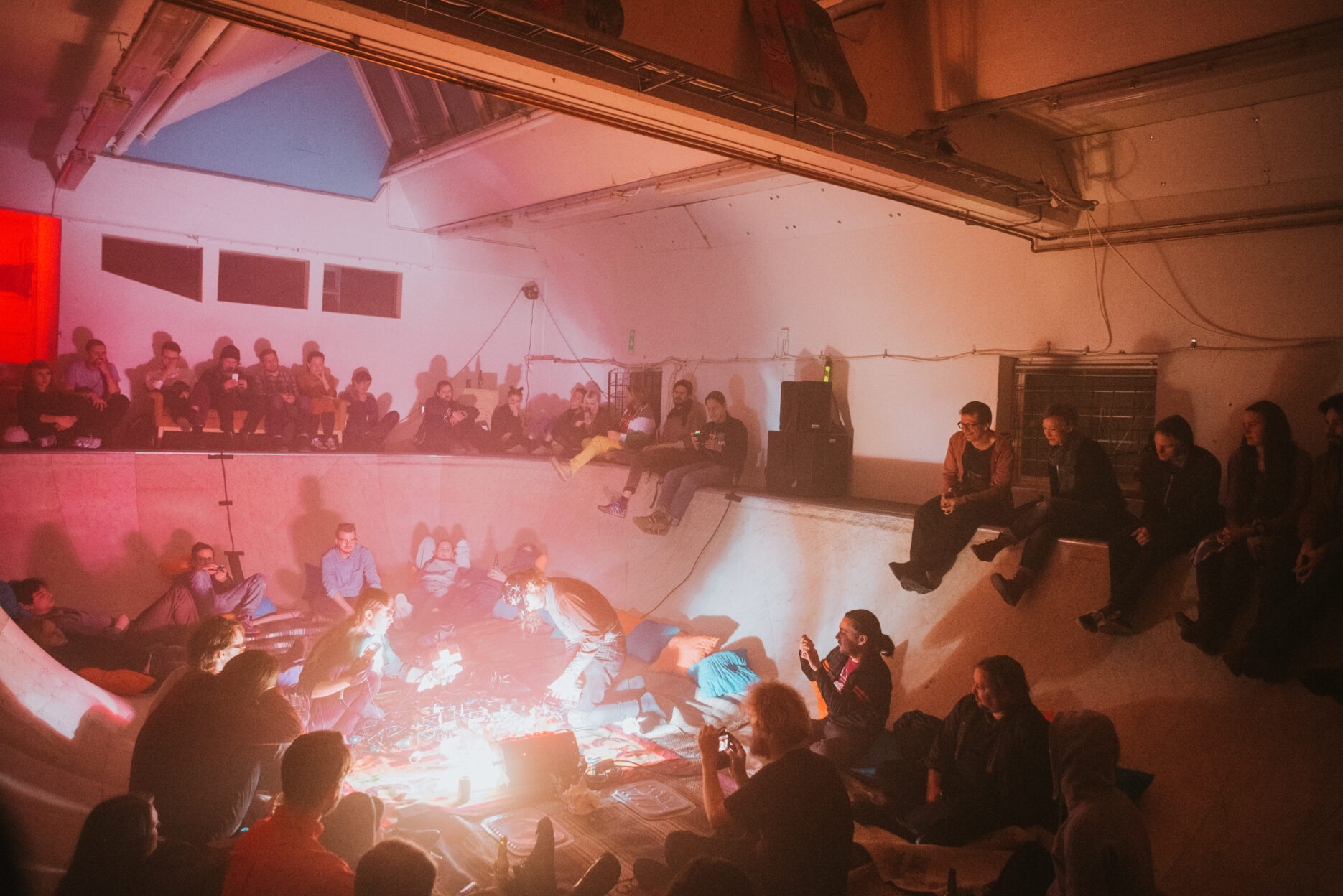 People sitting in an inside skate pool enjoying a concert with MSHR