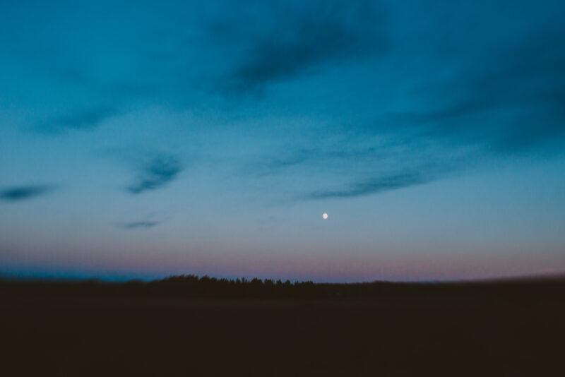 The moon against a darkening sky