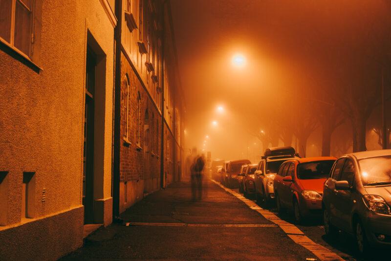 Person walking on a dark foggy street