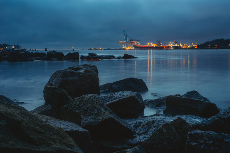 Stones at a coastline. Industrial cranes in the background.